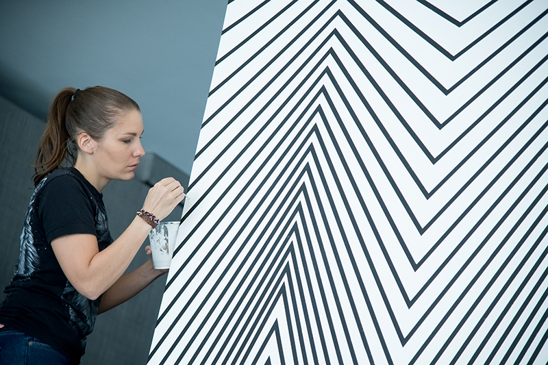 Claudia Comte installing 'Curves and Zigzags,' 2018. // Photo by Jon Gitchoff