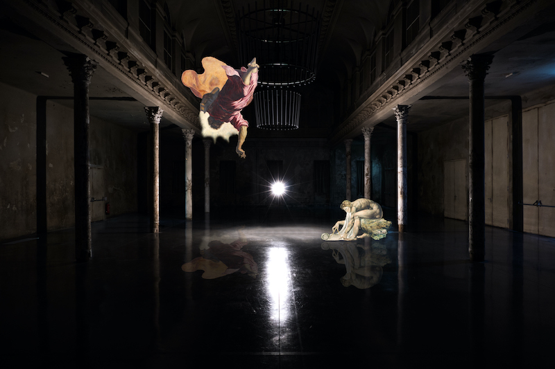 In a dark room an upside down figure is flying above a white orb. A marble statue is using a compass on the right hand side.