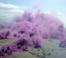 Purple smoke from fireworks rises over a vast beach