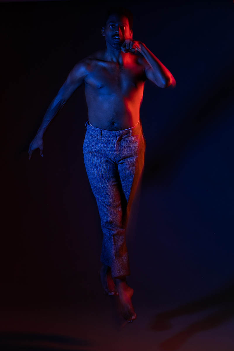 Color photo of Jerron leaping mid air in blue and red light, his left arm high near his face