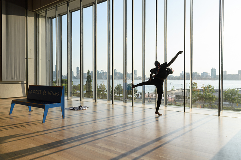 Color photo of Jerron in black leaping in the air against a wall of windows
