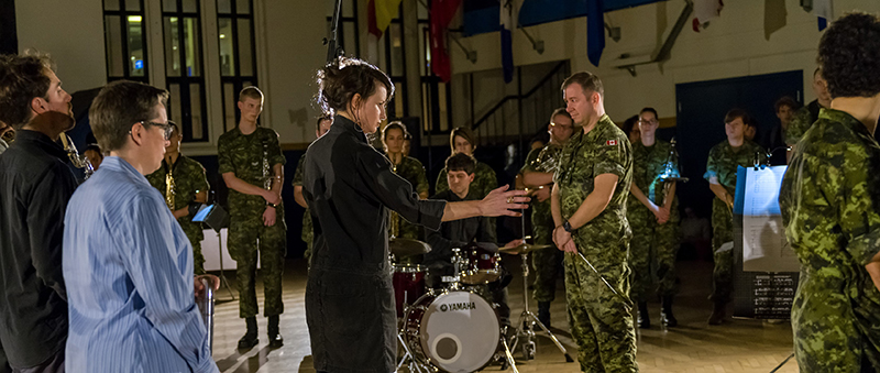 View of Marina Rosenfeld conducting the music performance in front of a group of military personnel in camo, a drummer, and the audience