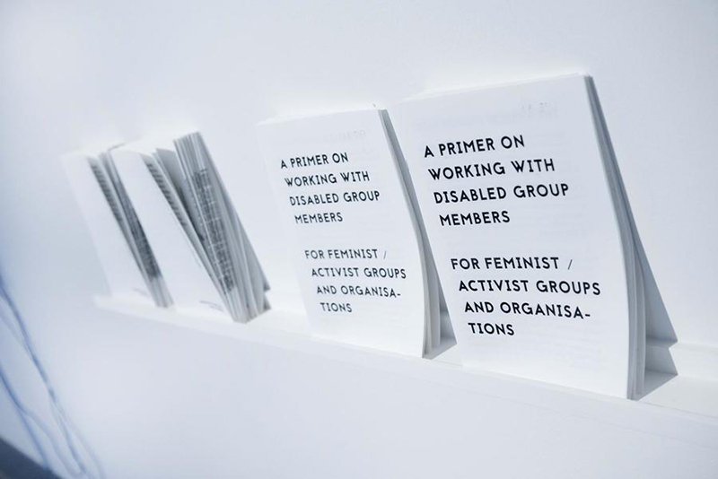 Multiple copies of a risograph pamphlet line a gallery wall.Romily Alice Walden's work 'A Primer on Working With Disabled Group Members for Feminist / Activist Groups and Organisations', 2018. 12 page, A4 risograph publication. Launched at AIR Gallery, NYC. Exhibited in the UK, USA, Germany and Poland. This document was produced in 2018 in response to experiences working with feminist and activist groups that were unprepared for working with disabled group members. The primer is an example of publishing as artistic practice; it positions information and education as a tool for change-making that can be embraced within a socially-engaged fine-art practice.