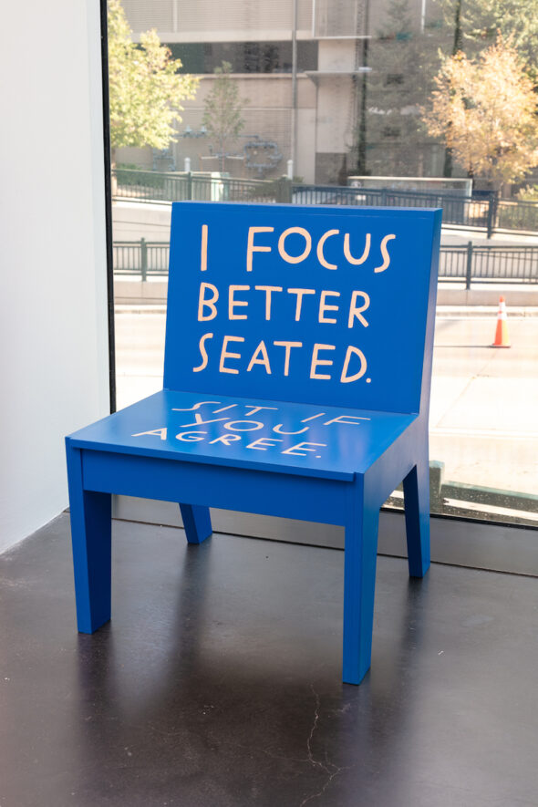 "A bright blue chair that says, ""I focus better seated. Sit if you agree."""
