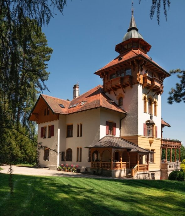 A traditional Alpine house with wooden shutters, a wood terrace and a spiraling turret is situated on a plot of lush green grass. Leaves from surrounding trees and a cloudless blue sky frame the image.