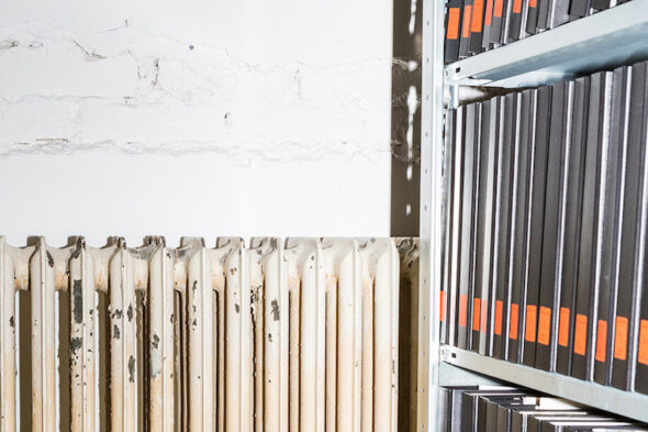 an abstract, close up photograph of an old and slightly damaged white radiator next to a shelf with a dozen black archival binders, each with an orange label on it