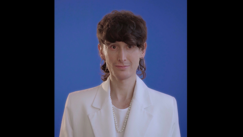 a still from a video portrait of the artist Manuel Solano wearing a white suit jacket over a white shirt, against a blue background, gaze focused on the viewer