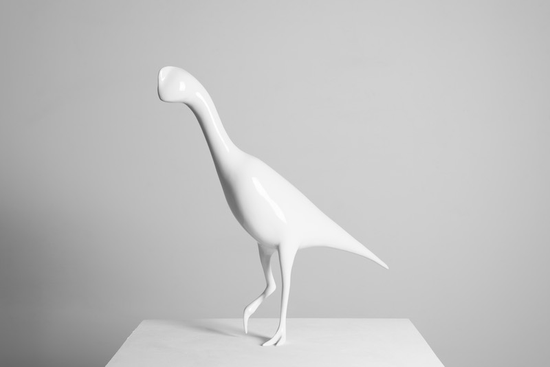 a white sculpture of a bird or dinosaur-like figure stands on a pedestal against a white wall
