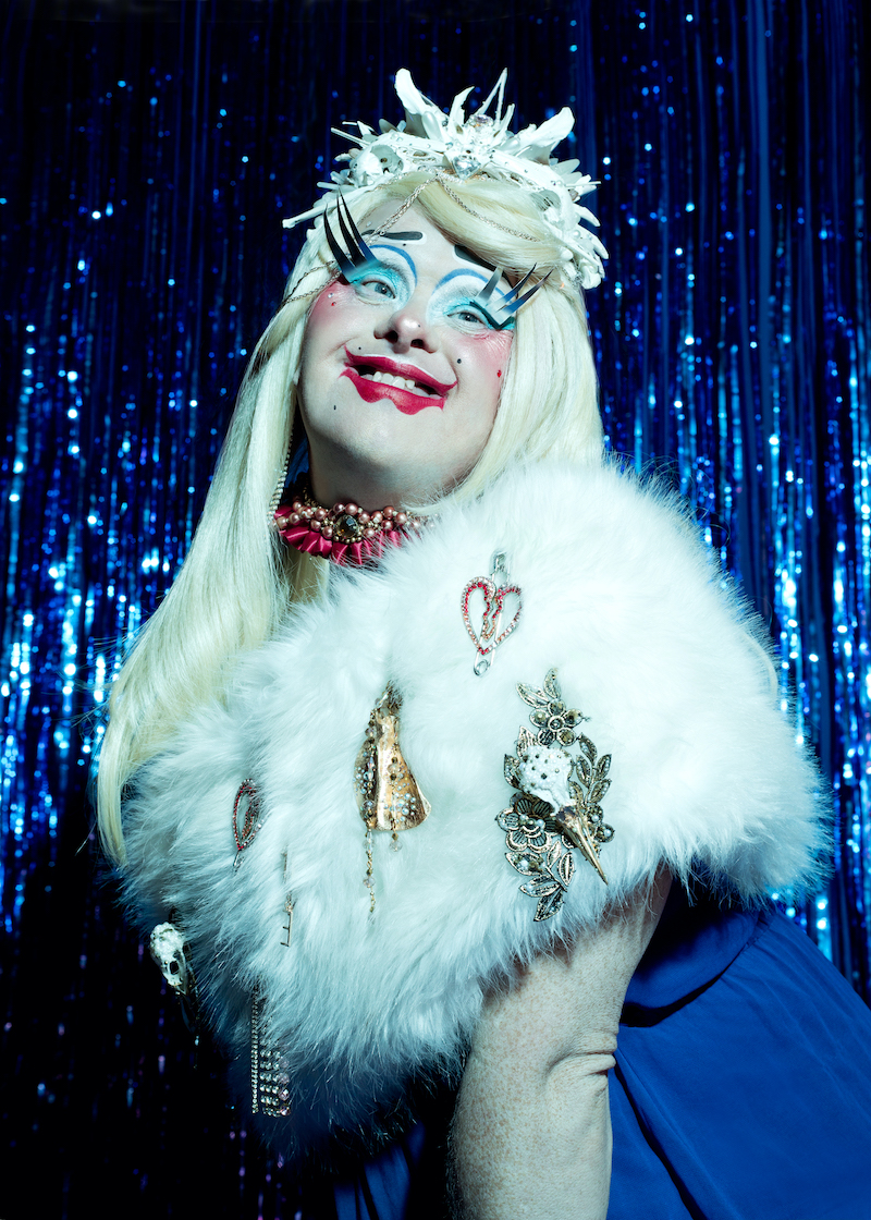 A performer from Drag Syndrome is photographed in the stage, wearing white faux fur, make und surrounded by blue fringe curtains