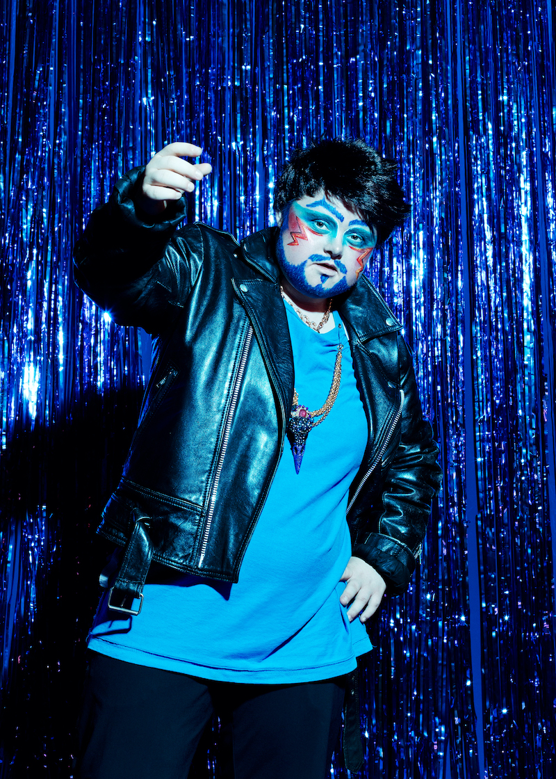 A performer of Drag Syndrome is wearing a blue t-shirt and black leather jacket