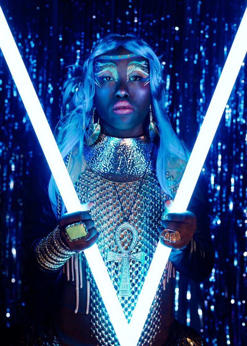 A performe of Drag Syndrome is holding neon light tubes, wearing a metal dress and a white wig