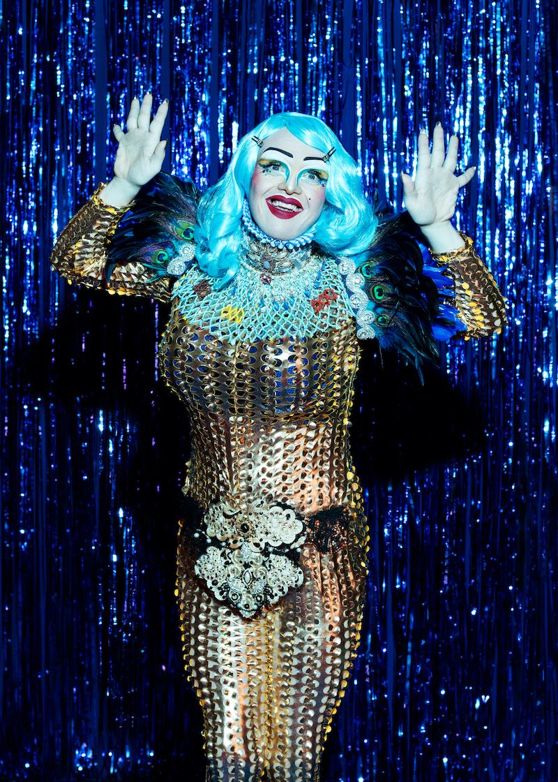 A performer from Drag Syndrome is photographed in the stage, wearing a golden dress and a blue fluorescent wig, make und surrounded by blue fringe curtains