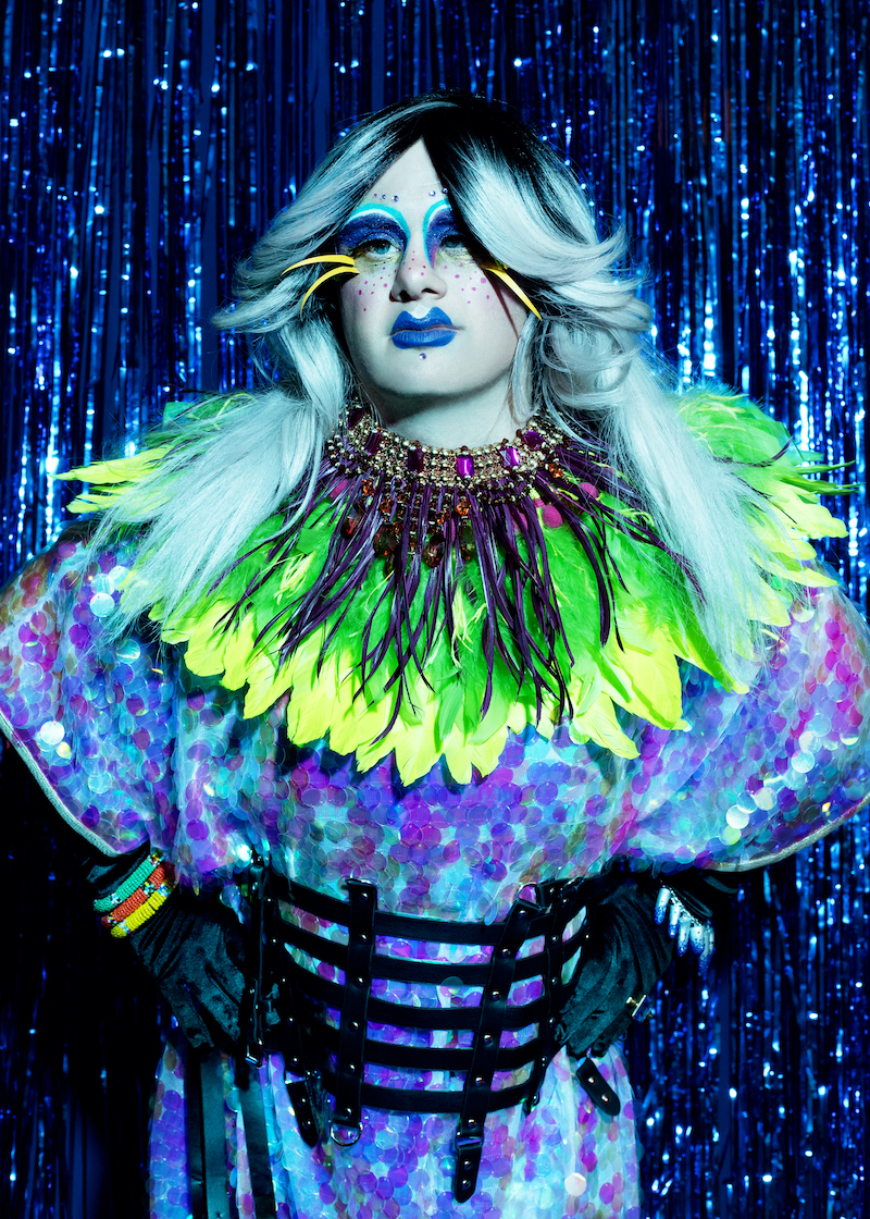 A performer from Drag Syndrome is photographed in the stage, wearing yellow fathers and purple and turquoise glitters, make und surrounded by blue fringe curtains