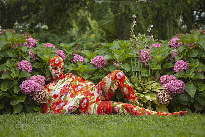a human lays in a floral body suit contrasting with pink hydrangeas in the background