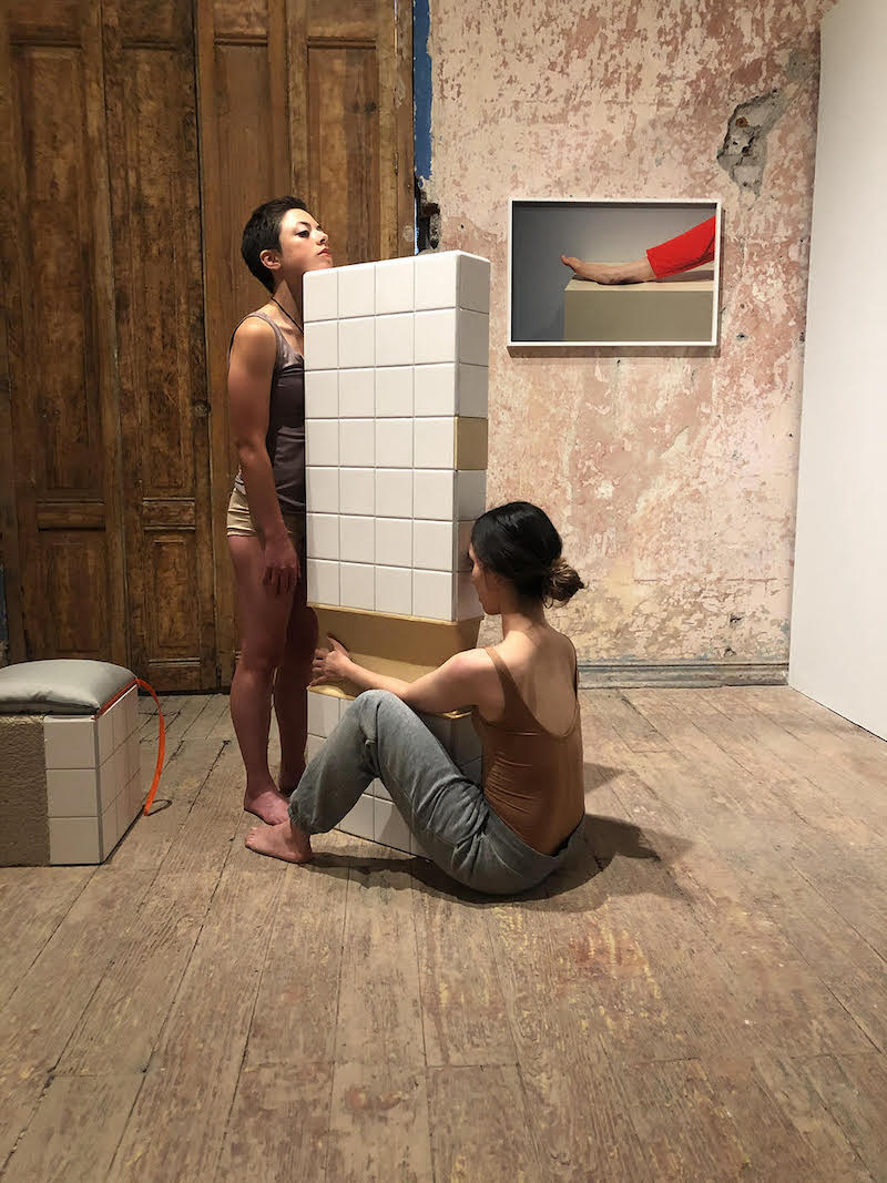 two women, one sitting, one standing, hold a tiled wall piece together