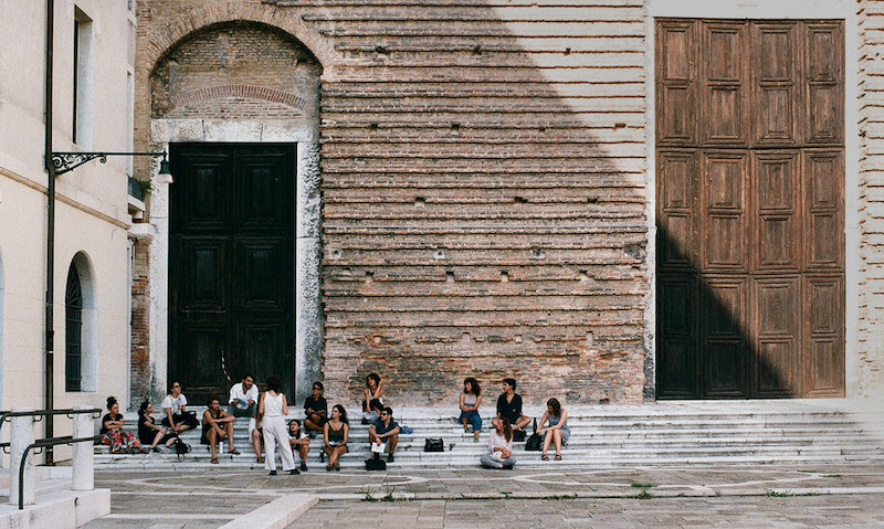people sit outside an old stone building in venice italy