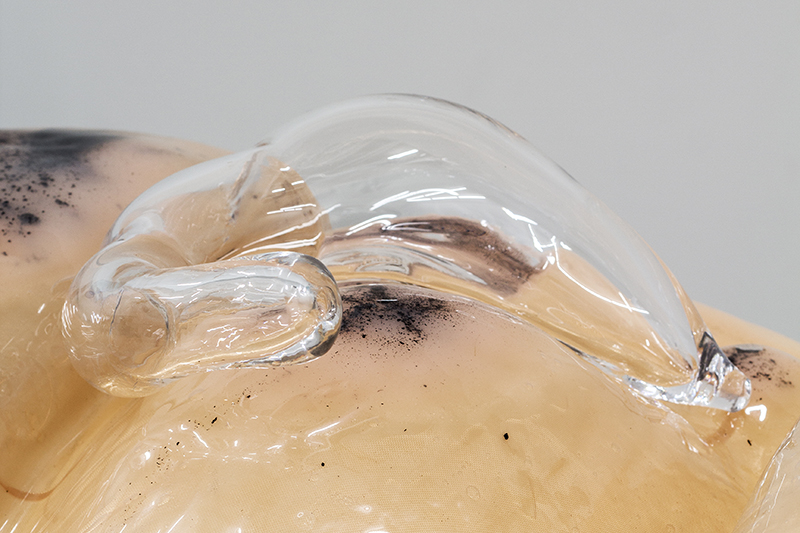 Close up of Pakui Hardware's sculpture 'Absent Touch', looks like skin with glass organs and a fluid substrate between layers of plastic and fabric
