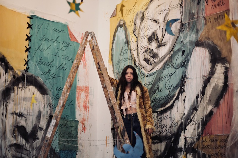 artist with long dark hair stands on a ladder in front of two large scale paintings of figures outlined in black and surrounded my pink, yellow and turqoise color blocks