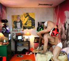 two men wrestling on a bed in a messy room
