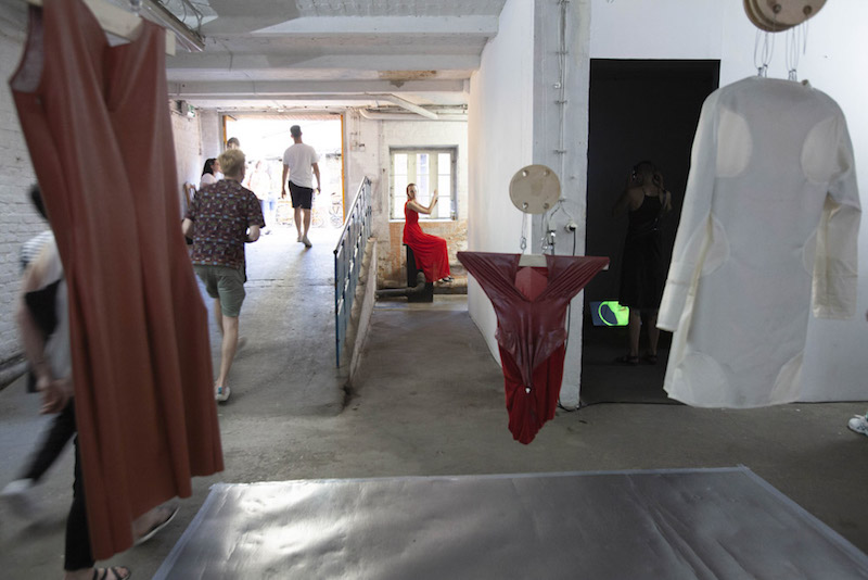 an art installation of hanging textiles in red and white tones shown in a gallery space
