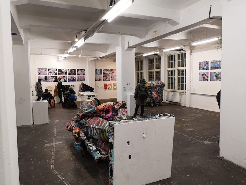 a large gallery space with bright white lights, an installation with coloured textiles in the foreground and photos mounted on the walls, several people looking at them, some standing, some in wheelchairs