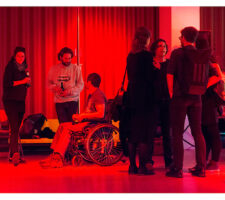 in a red-lit room with a curtain against the back wall, a group of people stand or sit in wheelchairs, speaking to each other and having a drink