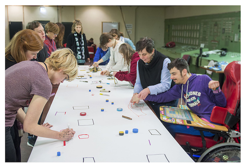 a group of artists stands or sits in wheelchairs around a long table with a white paper on it, drawing different and moving small pieces around