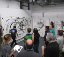 participants in a workshop for partially sighted and blind people in architecture pictured in front of two large wall canvases, with the teacher drawing black circular figures on them