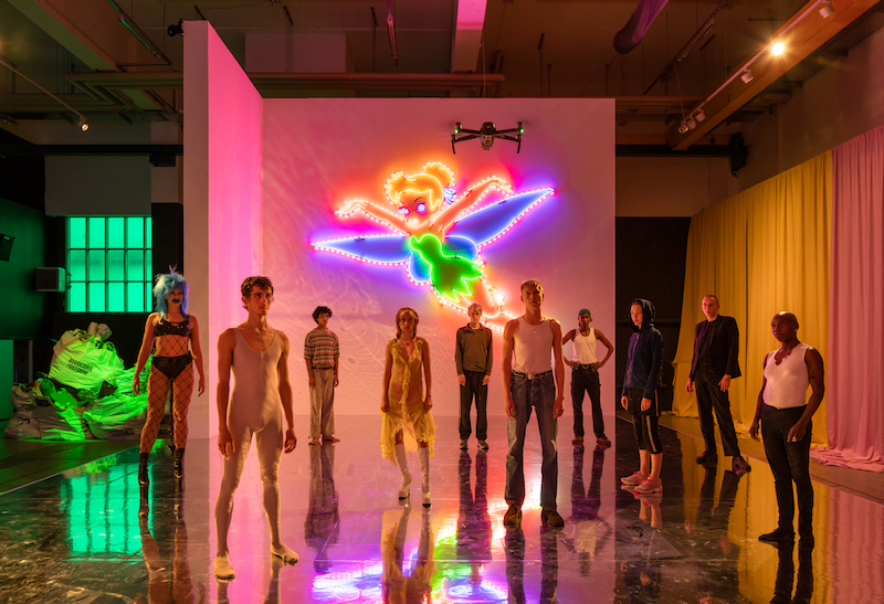 ten young performers are standing on a stage with mirrored floor and pink lighting, the light comes mostly from a large neon Tinkerbell mounted on a white wall behind them