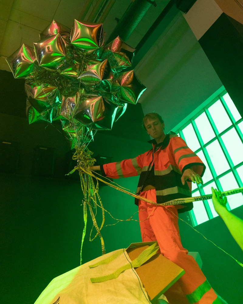 A person in hi-vis construction suit leans against a gridded window, while holding a large bunch of silver helium balloons