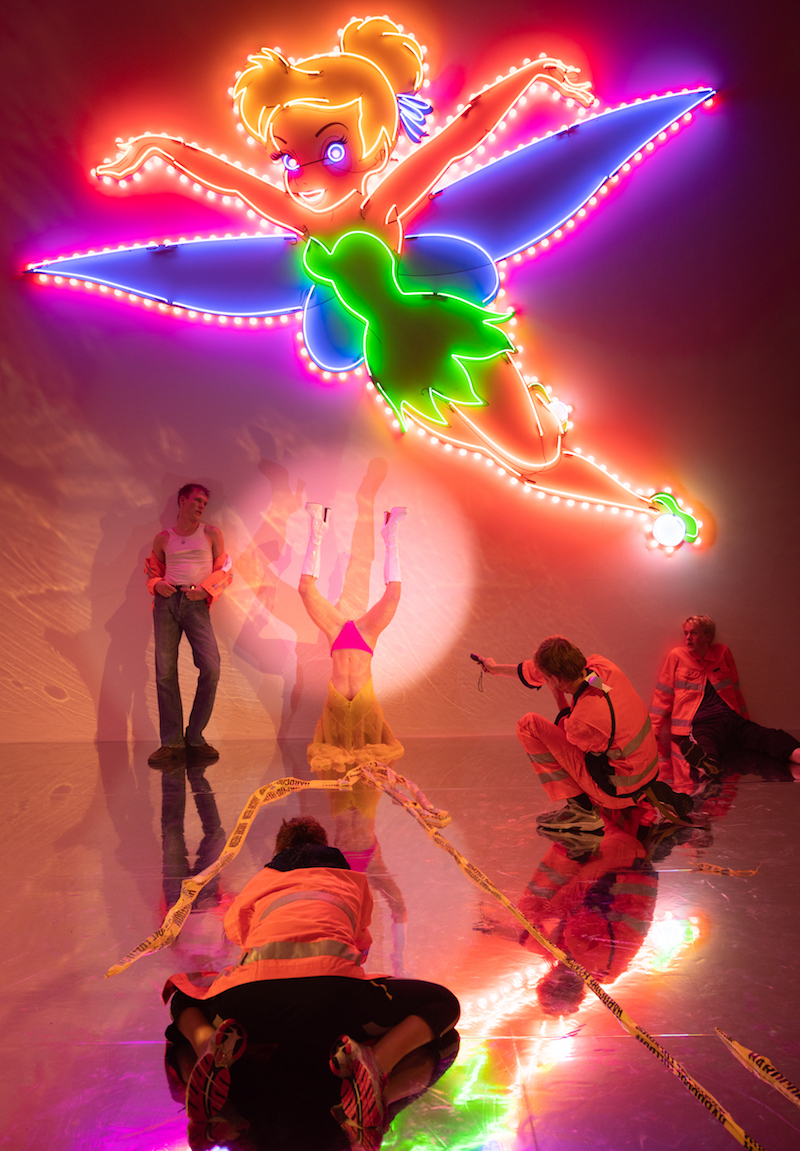 under a neon mounted tinkerbell light, several performers are dancing or draped on a mirrored stage