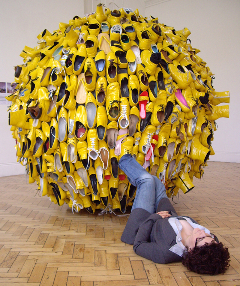 a person lies down on the floor of a gallery with her feet in the air, one foot is placed inside a shoe that forms part of a large, yellow, globe sculpture made up of shoes