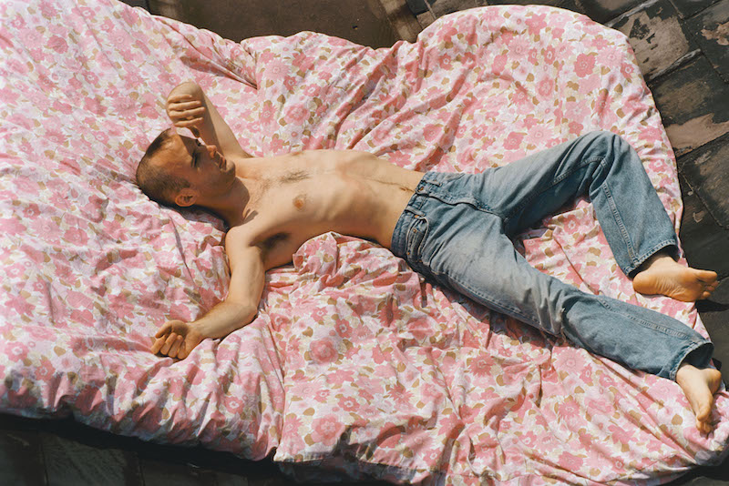 a shirtless person with a shaved head and wearing only pale blue jeans lies on a bed, on top of a rose coloured, flower pattern duvet