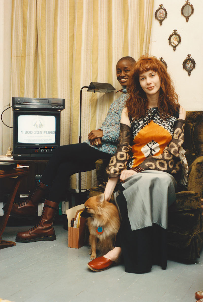 two people sit on a lazy boy next to an old television set, with a small dog between them on the floor