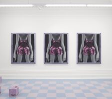 three identical portraits of a woman in a sequined dress are mounted on a gallery wall, with a checkered floor in the foreground and some undefined mauve box sculptures on the floor