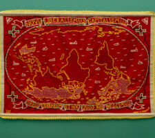 "A detailed shot of a tapestry, embroidered with a map reading ""novu imperialismus capitalismus"" across the top is mounted on a green gallery walll"