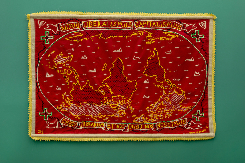"""A detailed shot of a tapestry, embroidered with a map reading """"novu imperialismus capitalismus"""" across the top is mounted on a green gallery walll"""