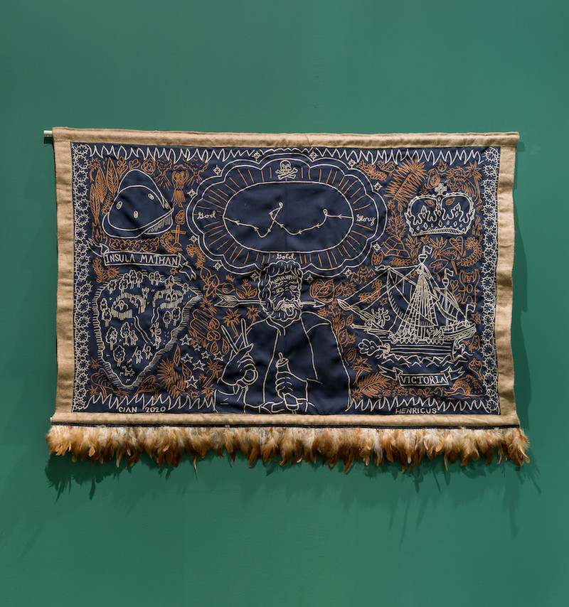 an embroidered textile artwork in deep navy and rust colour, showing an unknown map, is mounted on a forest green gallery wall