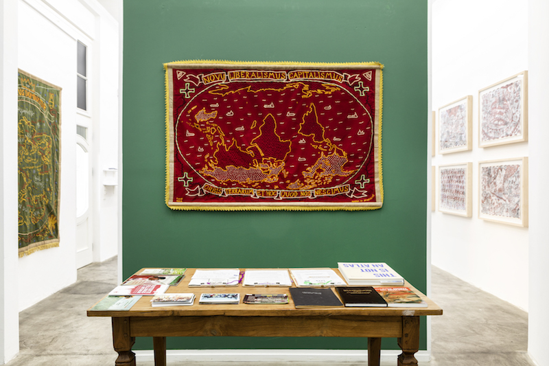 a red textile embroidered map, hard to make out in detail, is mounted on a forest green gallery wall. a table of literature sits in front of the artwork