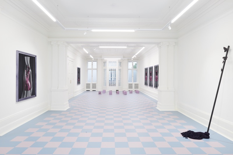 a wide angle shot of a gallery space with works mounted on the wall and a pale blue and pink checkered floor