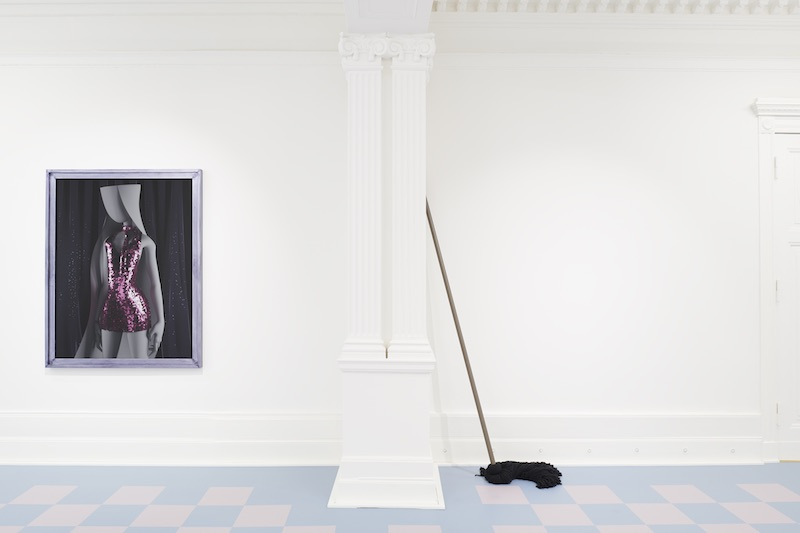 a portrait mounted on a white gallery wall, beside an oversized black mop, which leans against the wall
