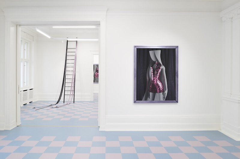 a portrait of a girl in a sequined dress mounted on a white gallery wall, with a ladder coming down from the ceiling in the background