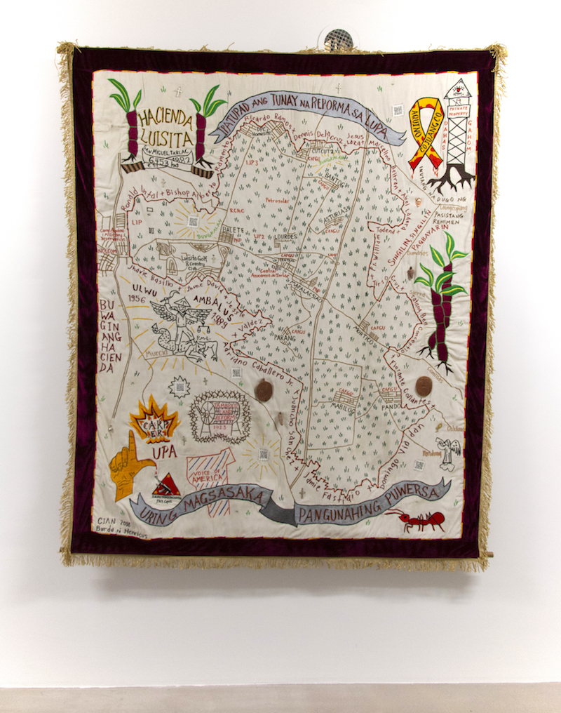 a colourful embroidered tapestry showing an unknown map is mounted on a white gallery wall