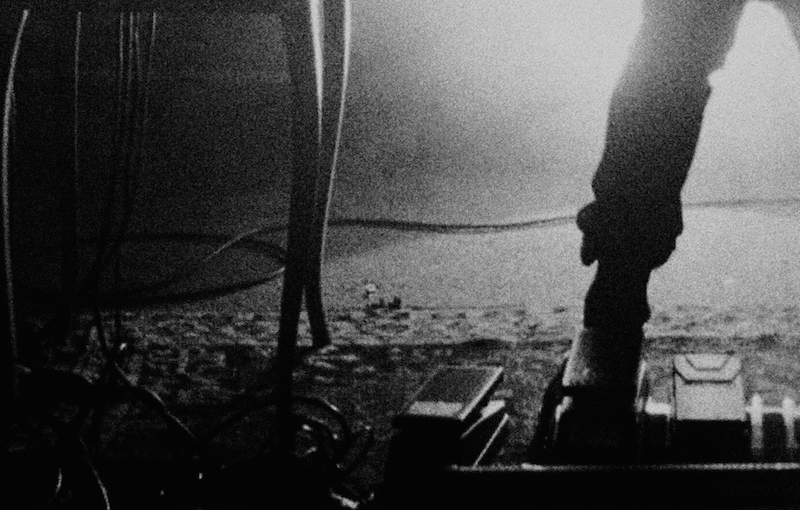 a black and white photograph of a foot on a music pedal under a table