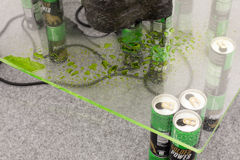a transparent table is partially shown, held up with cans of green energy drinks instead of table legs, a mass of cords under it. there is a spilled green liquid on the table top