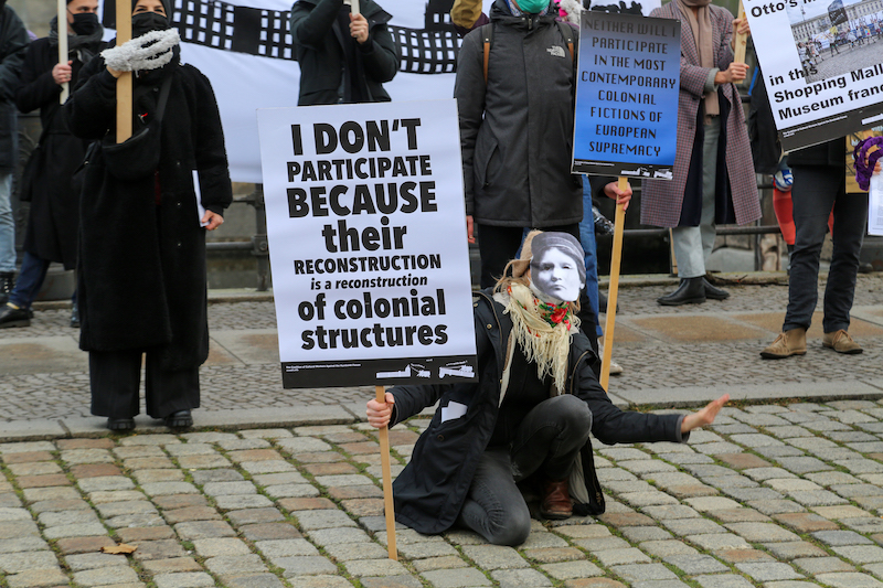 A person wearing a face mask kneels while holding picket sign 'I don't participate because their deconstruction is a reconstruction of colonial structures'