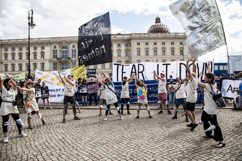 a group of protestors in smocks hold flags and signs in a half circle and have their arms up, performing a song