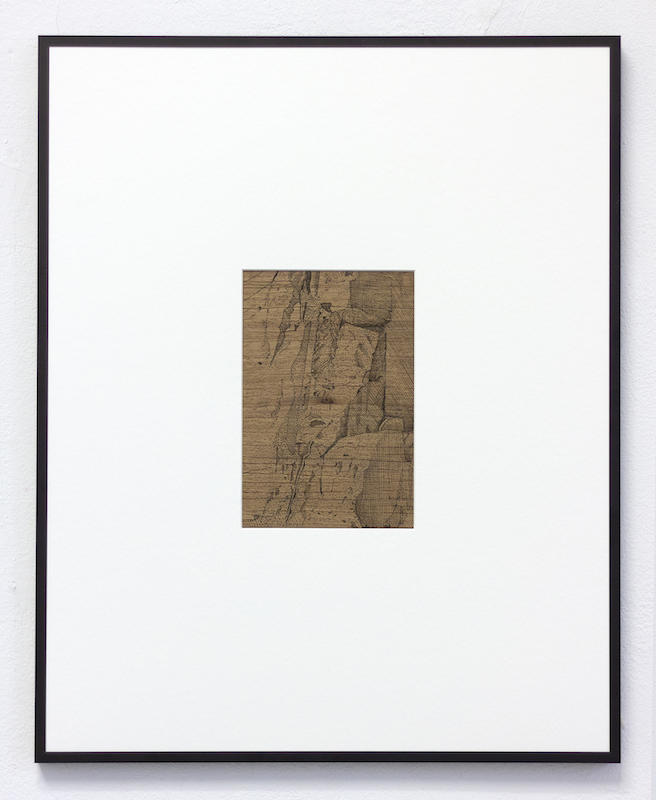 A framed photo of a black line drawing on brown wood of a bunker.