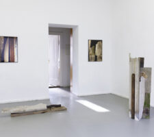 A view of the exhibition featuring two sculptures and two photographs in a white room.