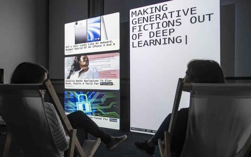 """A photo of two people looking at computer screens reading """"making generative fictions out of deep learning""""."""